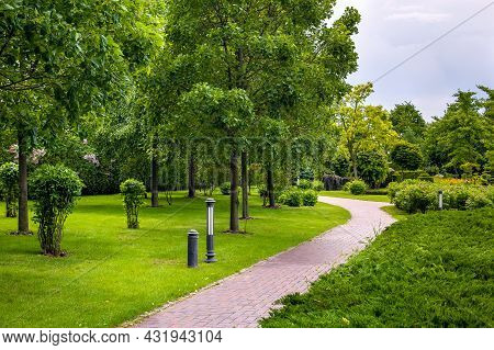 Stone Tile Walkway Curve Arcing In The Park Among Green Plants Of Evergreen Thuja Hedges And Trees W