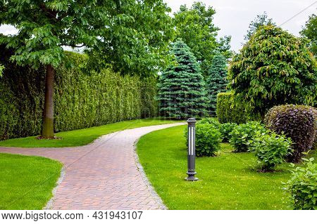 Stone Tile Footpath Curve Arcing In The Park Among Green Plants Of Evergreen Thuja Hedges And Trees