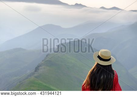 Woman With Long Hair And A Hat Relaxing In A Amazing Mountains With Fog. Wanderlust And Travel Conce