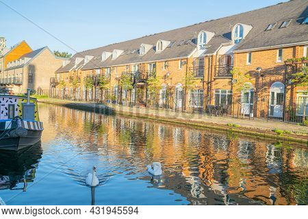 Canal-side Apartments Reflected In Calm Water In Morning Light With Two White Swan On Shady Side Of