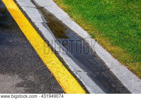 Puddle On Drain Canal Near Asphalt Road With Stormwater On The Road Side With Ditch For Water After