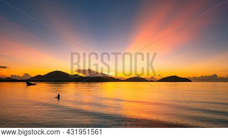 Beautiful Sunset Or Sunrise Over Sea With Silhouette Of Fisherman In The Sea Mountain Background At