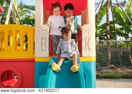 Asian Cute Brother And Sisters Having Fun Playing On A Slide In Playground At Home Backyard On Summe