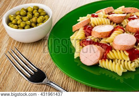 Bowl With Green Peas, Fork, Plate With Boiled Pasta Fusilli, Fried Sausages And Tomato Sauce On Wood