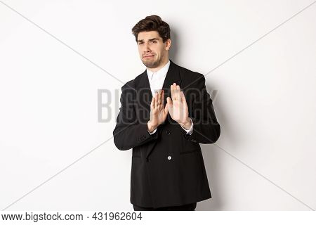 Image Of Stylish Handsome Man In Black Suit, Cringe From Something Embarrassing, Declining Offer And