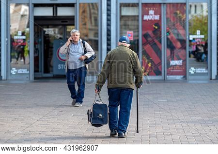Riga, Latvia - September 3, 2021: Elderly Man With Cane Walking Down The Street, Rear View, Concept