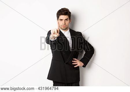 Portrait Of Serious Handsome Man In Business Suit, Showing One Finger To Prohibit Or Decline Somethi