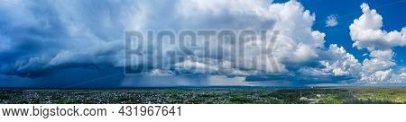 Panoramic picture of beautiful cloudscape under the village. Heavy white clouds in the blue sky.