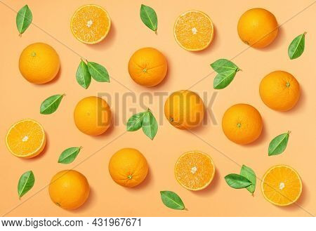 Fruit pattern arranged of oranges and orange leaves on yellow background. Lay out background.
