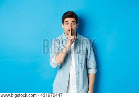 Portrait Of Excited Man Asking To Keep Quiet, Showing Hush Taboo Sign And Looking Nervously At Camer