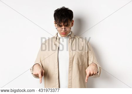 Confused Frowning Guy In Glasses Looking, Pointing Fingers Down At Something Strange, Standing Puzzl