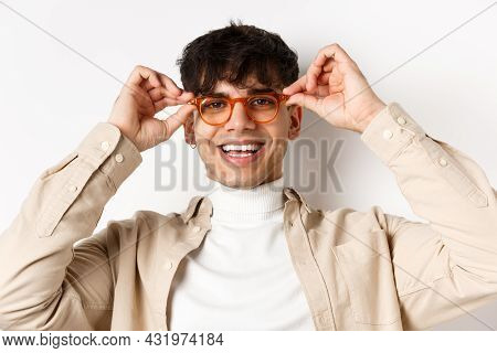 Close-up Of Stylish Hipster Guy Trying Eyewear At Optician Store, Put On Glasses And Smiling, Standi