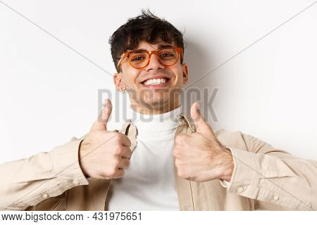Close-up Of Satisfied Happy Guy Showing Thumbs Up And Smiling With White Teeth, Wearing Eyewear, Sta