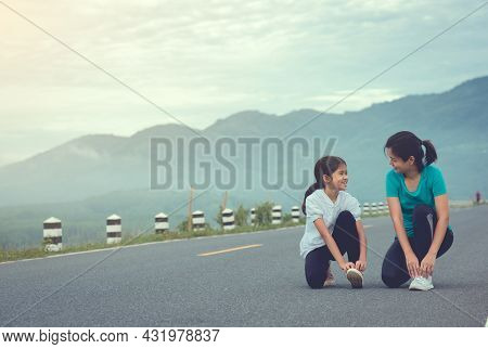 Mom And Child Are Kneeling And Tying Shoelace. We Getting Ready For Jogging Outdoors The Time During