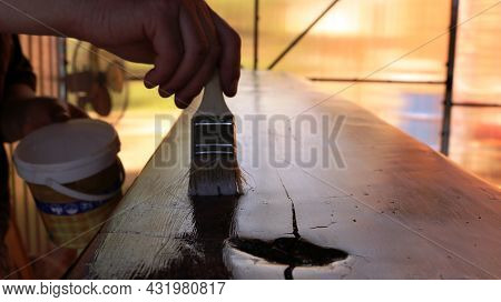 A Varnisher Covers The Textured Surface Of Furniture With Varnish From A White Can Using A Narrow Br