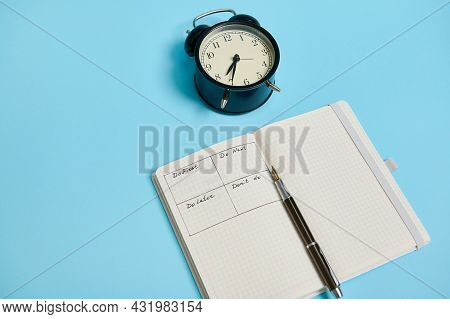 An Open Organizer Notebook With Timetable Of The Day By Hour, Pen, Alarm Clock On Colored Background