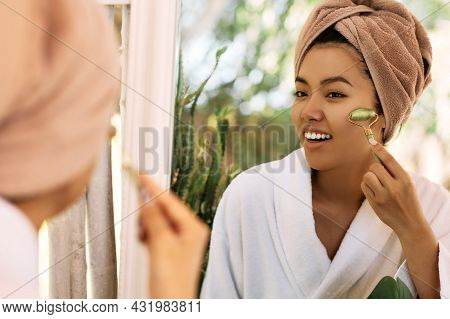 Young Asian Woman Massages Her Face Using A Green Jade Roller, In Reflection Of A Mirror. Facial Jad