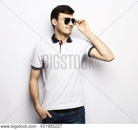 Elegant handsome man in smart casual wear and sunglasses.
