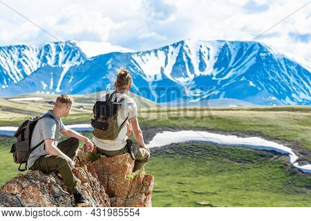 A Group Of Two People Tourists Or Climbers With Backpacks Sit On The Top Of The Mountain Looking Ove