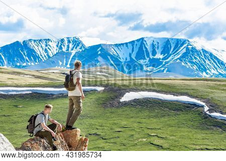 A Team Of Two Tourists, Men Or Climbers With Backpacks, Stand On The Top Of The Mountain And Enjoy T