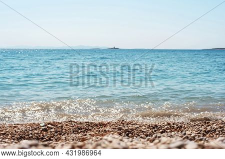 Beautiful Pebble Beach And Blue Sea With Islands. Shallow Depth Of Field.