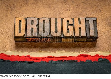 drought word abstract in vintage letterpress wood type against abstract desert paper landscape, environment and climate change concept