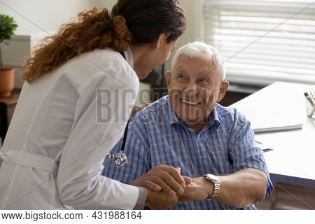 Friendly Doctor And Optimistic Elder 80s Man Meeting In Office