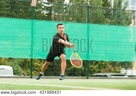 A Male Tennis Player Is Elegantly Hitting A Tennis Ball. A Tennis Player Who Looks Like A Dancer.