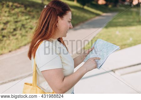 Attractive Young Female Tourist Is Exploring New City. Happy Redhead Woman With Map In Hands