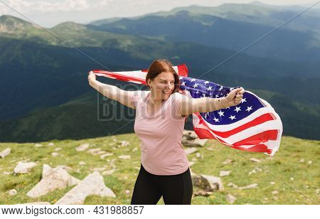 Girl With American Flag Looking Out At Landscape. Young Woman Stands In The Mountains, Holding The U