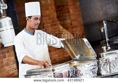 Adult arab chef man in uniform demonstrating food on cooker in resort hotel restaurant kitchen