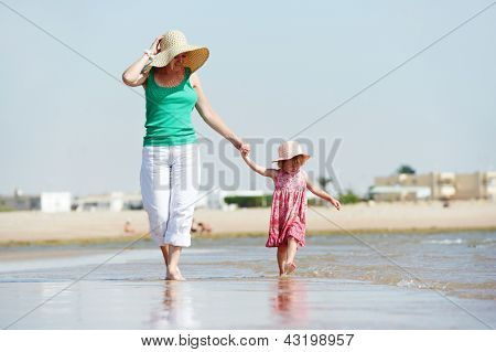 woman mother walking with little child girl on sea ocean beach at vacation