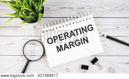 Operating Margin Text Concept Write On Notebook With Office Tools On The Wooden Background