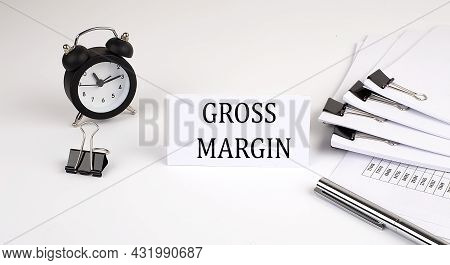 Card With Text Gross Margin On A White Background, Near Office Supplies And Alarm Clock. Business