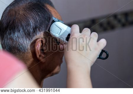 Old Man Having A Hair Cut By Hairstylist Using Electrical Battalion. Men\'s Hairstyling And Hair Cut