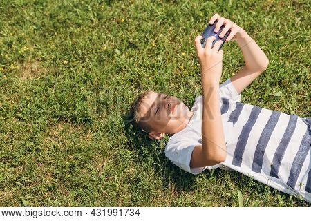Outdoor Portrait Of Blond Boy Teenager, Male Young Man Texting Or Using Social Media On Cell Phone O