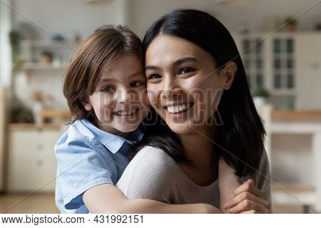 Happy Cute Small Boy Cuddling Beautiful Asian Korean Mother.