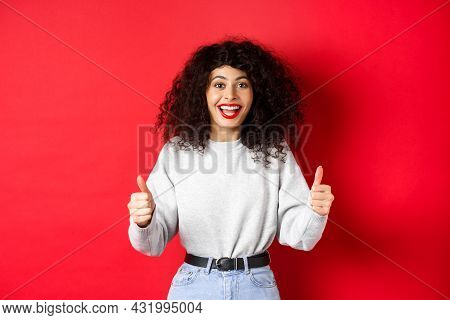 Enthusiastic Girl With Curly Hair And Red Lips, Showing Thumbs Up And Saying Yes, Agree With You, Co