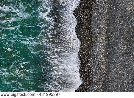 Green Sea Waves Break On Black Sand And Pebbles Shore, Aerial Marine Texture
