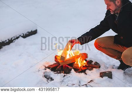 Mature Man Warming His Hands With Fire After Making Campfire In Middle Of Snowy Forest In Cold Winte