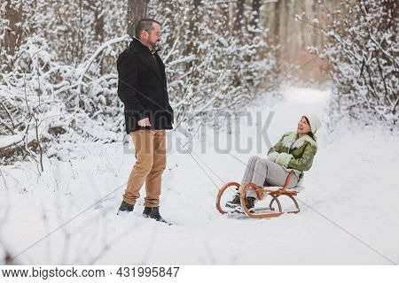 Happy Playful Mature Family Couple Sledding In Winter Park, Laughing And Having Fun Together, Positi