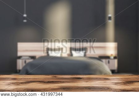 Wooden Table With Modern Grey Bedroom Interior On The Background. Two On Trend Pendant Lights And A