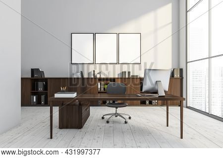 Three Empty Posters In The White Office Interior With A Dark Wood Desk With An Office Chair And A Si