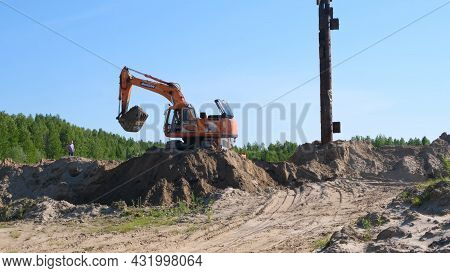 Yellow Excavator Bulldozer Carries Out Excavation Of Sand Digging At Construction Site: Moscow, Russ