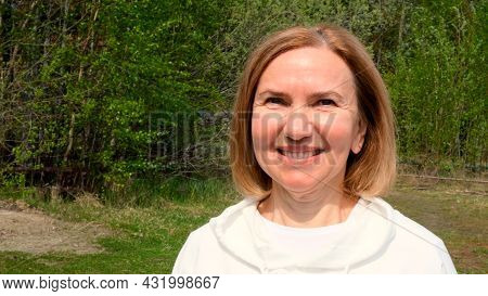 Beautiful Mature Woman Face. Mid Adult Lady Smiling Outdoors. Portrait Of Female Age 55-60 Relaxing