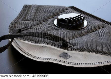 A Black Respirator With Filter And Valve Lies On A Gray Uniform Background. Respirator Protection Cl