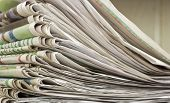 closeup pile of newspaper on wooden background poster