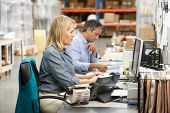 Business Colleagues Working At Desk In Warehouse poster