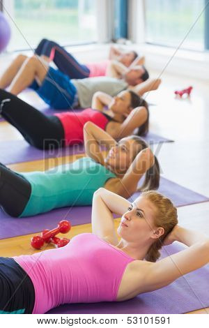 Side view of sporty fitness class doing sit ups on exercise mats