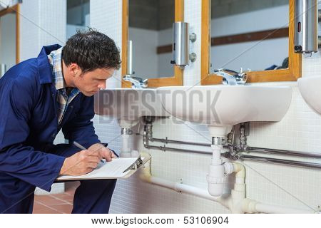 Handsome plumber looking at sink holding clipboard in public bathroom